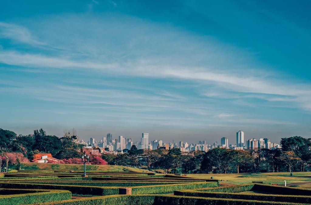 Vista da cidade de Curitiba, de dentro da estudo no Jardim Botânico, veja mais fotos de como fica esse icônico ponto turístico na florada das cerejeiras!Clique para ler! #Curitiba #Cerejeiras #JardimBotânico