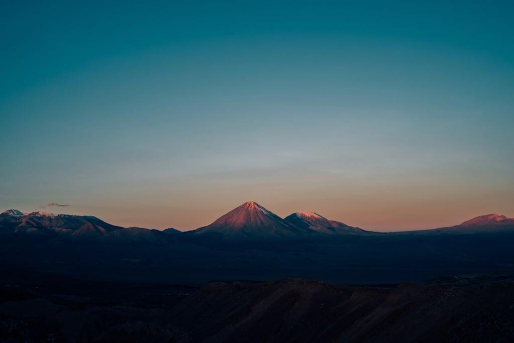 Imagem de vulcões do Valle de La Muerte, Atacama. Iluminados pelo pôr do sol, formam uma imagem incrível. #atacama #desert #sky #pordosol