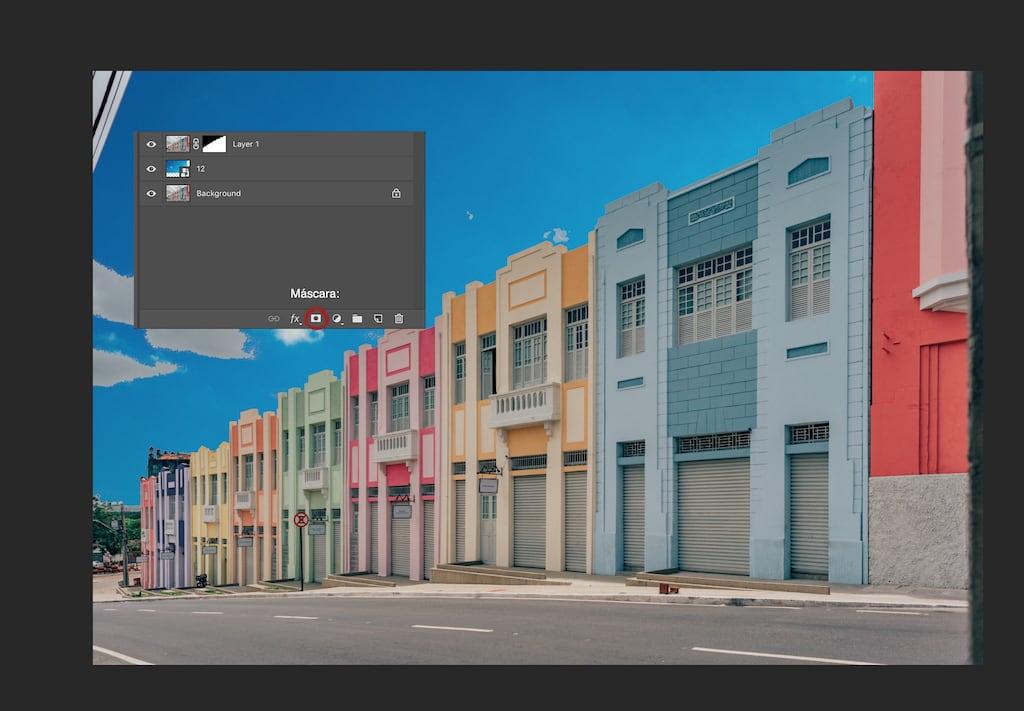 Criando uma máscara no photoshop para mudar o céu. Após inserir a imagem do céu, selecione a área a ser modificada e clique no ícone, mesclando as camadas. Veja o tutorial completo no blog.