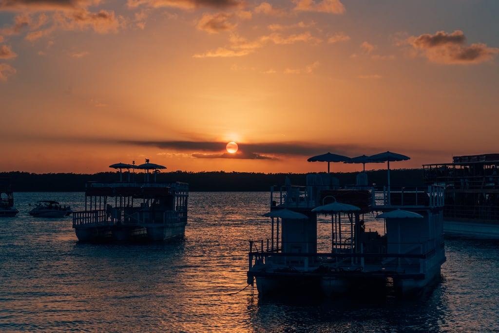 Um homem com roupas brancas está de costas sobre um barquinho indo em direção ao meio do rio. Ao fundo, vemos catamarãs e o céu dourado no fim de tarde.