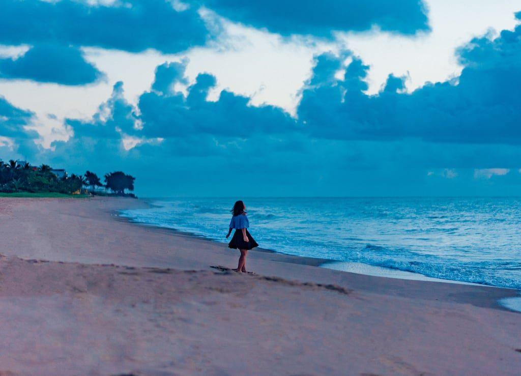 A praia de Manaíra, pouco antes do amanhecer, ainda com as luzes da cidade acesas e um tom azulado no céu. Vale a pena assistir ao nascer do sol nessa bela praia de João Pessoa! Veja mais fotos no post.