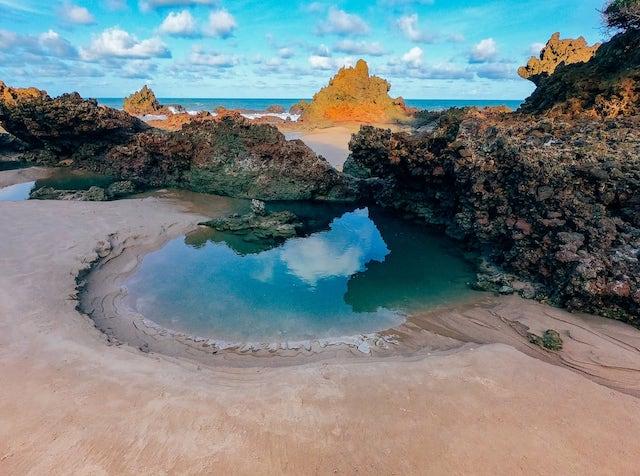 Belos reflexos numa poça de água formada pelas rochas! Conheça mais sobre essa praia no link!