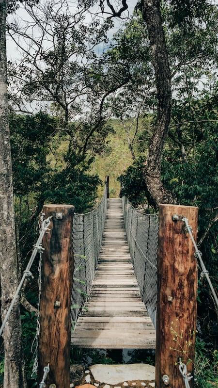 Ponte pênsil na trilha do vale, passeio repleto de mirantes e cachoeiras em Pirenópolis-GO! Clique para saber mais.